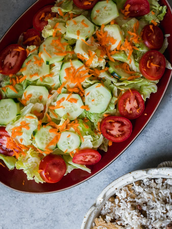 Salad with lettuce, cucumbers, tomatoes and shredded carrots.