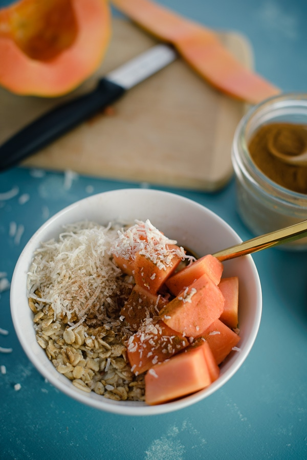 Un plato de avena con papaya y coco.
